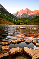 Sunrise on the North and South Maroon Peaks. Maroon Lake with rocks in the foreground. Maroon Bells Scenic Area.