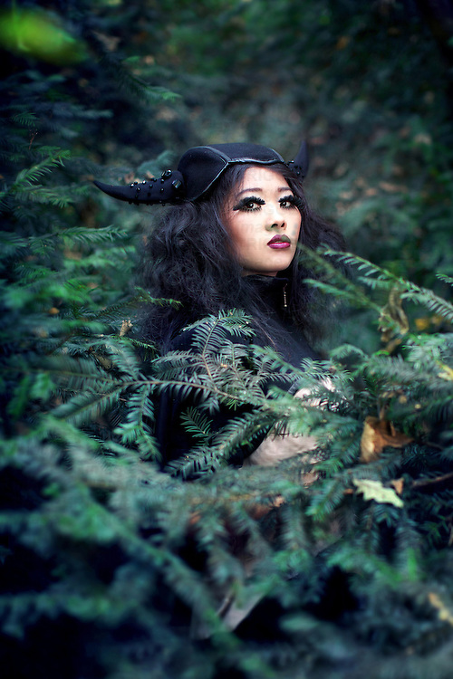 A girl in a horned hat and dark costume stood amongst fir trees in a forest.