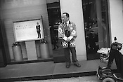 Man standing with folded hands outside of a bank, Tokyo, japan