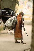 A woman walks the winding narrow streets of Kolkata with her belongings in a sack. Formally known as Calcutta, the city is the third largest most populated metropolitan area in India and the capital of West Bengal.