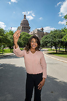 Beautiful businesswoman taking selfie picture of herself against the Texas State Capitol in downtown Austin, Texas, selfie.
