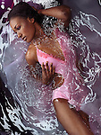 Beautiful black woman wearing a pink swimsuit lying in shiny water