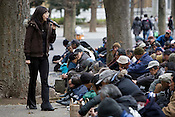 Homeless men listen to a religious sermon from a volunteer woman at a soup kitchen. Approximately 700 homeless men attend a soup kitchen run by a Korean Christian church, in Ueno Park, Tokyo, Japan, Friday 27th March 2009. The men, most of whom are long term homeless, attend the soup kitchen 4 times a week, and have to listen to a church sermon prior to being given a hot lunch, food to take away, and if they wish they can have haircuts, and obtain clothes.