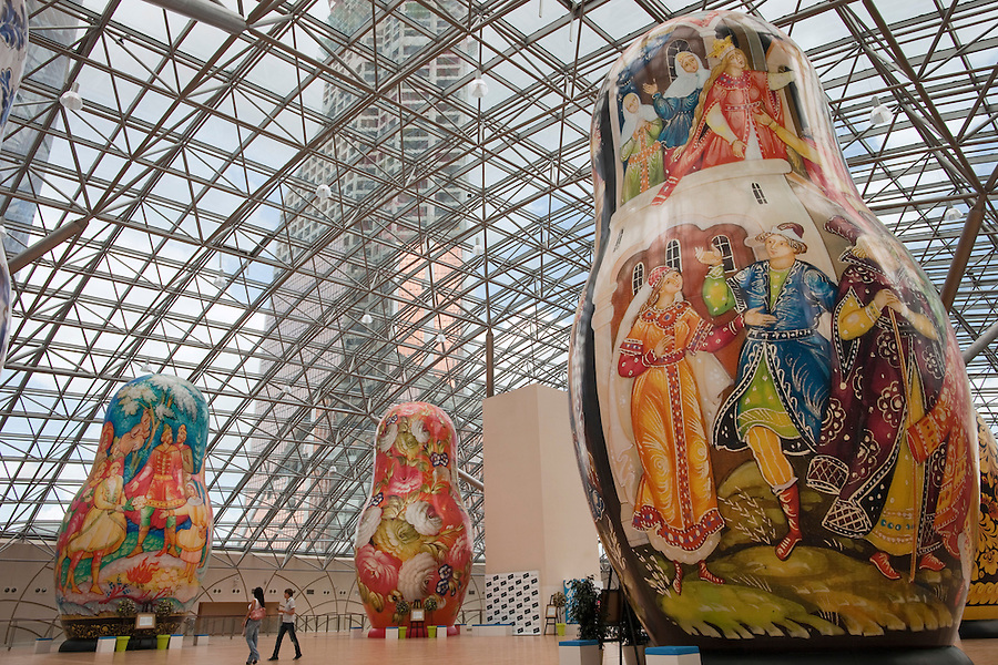 Moscow, Russia, 15/06/2011..People walk through an exhibition of of giant Russian matryoshki, or nesting dolls, in the newly-opened Afimall shopping centre. The dolls, designed by Boris Krasnov, are from 6 to 13 metres high, and each is decorated in a different style of traditional Russian folk art..Left - right: Mstero, Ornamental Zhostovo painting, and Palekh styles..