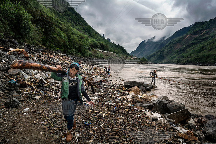 Lisu villagers collect driftwood, deposited in the river by recent landslides caused by heavy rain, from the bank of the Nujiang River.