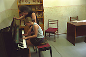 A young girl is helped in her piano lessons by her tutor in the Boris Nadezhdin Music School in Tashkent, one of the Central Asian cities on the old SIlk Road trading route. Uzbekistan.