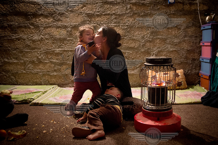 Aida kisses her 2 year old daughter Haine at night inside her temporary house where they are living with her parents and her husband. <br /> Aida, a 21 year old mother of two small children, was captured with her one year old son and two year old daughter by Islamic State (IS) fighters in Sinjar when IS invaded the city in August 2014. During her two months in IS captivity she was moved around frequently to various towns in the region. They were often beaten and one day an IS fighter pointed a gun to her daughter's face. 'One day I stole a mobile phone at the IS house and called my family.... My husband asked one of his Muslim friends to help him rescue me.... When everything was ready I ran away from the IS house and was rescued by my husband's friend one km from where I was captured. My family paid $ 4,000 to two people who picked up myself and my children and drove us to a safer area. We lost everything.' Aida is now living with her parents in a small house they are renting near Dohuk. Her mother in law is still in IS captivity. Her father was killed in front of her by IS fighters.
