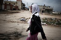SYRIA - Al Qsair. A woman walks in a street as Al Asad Forces are shelling the city of Al Qsair, on February 23, 2012. ALESSIO ROMENZI