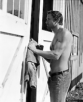 shirtless man entering a barn