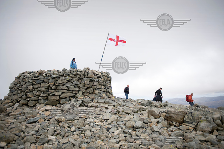 Hikers and an English flag on the peak of Scafell Pike in the Lake District National Park in Cumbria.