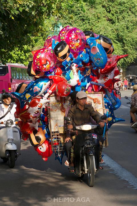 Phnom Penh, Cambodia. Balloon seller on a motorbike.