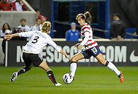 US forward Alex Morgan (13) attempts to maneuver around Germany's Saskia Bartusiak(3).  The U.S. Women's National Team tied Germany 1-1 in a friendly at Toyota Park in Bridgeview, IL on October 20, 2012.
