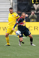 Mar 26, 2011; Columbus, OH, USA; Columbus Crew midfielder Dejan Rusmir (22) knocks down New York Red Bulls midfielder Joel Lindpere (20) during their match at Columbus Crew Stadium. The game finished in a 0-0 tie.