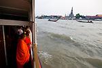 Chao Phraya River, Bangkok, Thailand. Monks looking at Wat Arun from the Orange Flag Express Boat