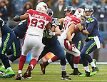 Seattle Seahawks quarterback Russell Wilson readies to pass downfield while being pass rushed by Arizona Cardinals defensive end Calais Campbell (93) during the 3rd quarter at CenturyLink Field in Seattle, Washington on December 22, 2013. Wilson completed 11 of 27 passes for 108 yards and threw for one touchdown and had one pass intercepted in the Seahawks 10-17 loss to the Cardinals.  .©2013. Jim Bryant Photo. ALL RIGHTS RESERVED.
