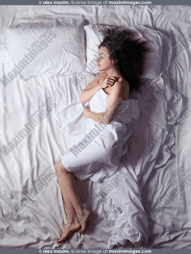 Overhead photo of a young woman sleeping alone in bed covered with a bedsheet in a bedroom lit by the morning sunlight