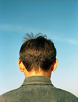 Rear view of a young boy wearing a denim shirt.<br />