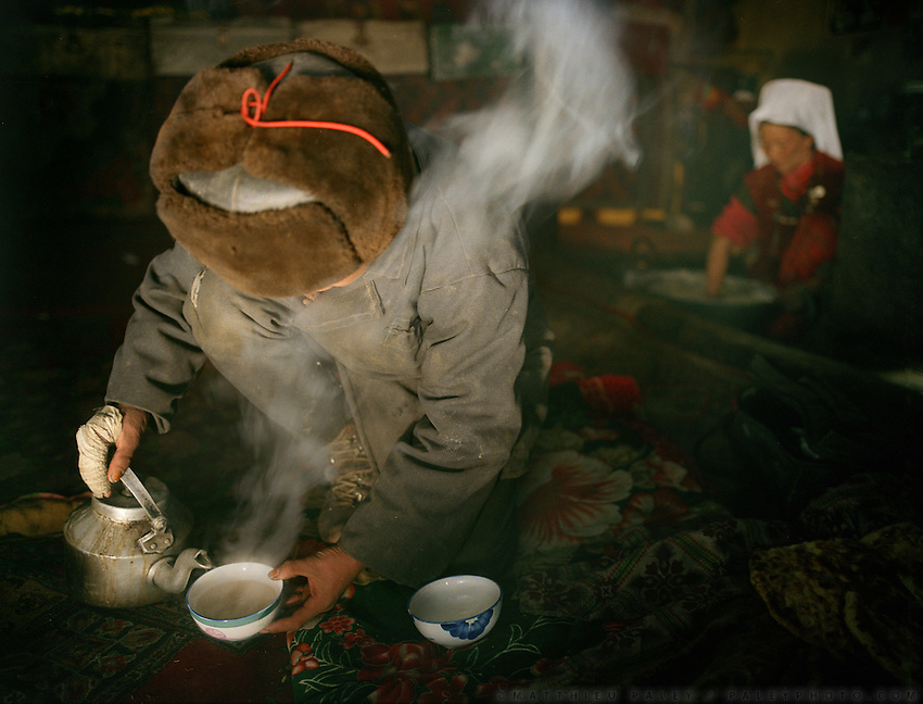 Mujaheed, son of Khan, serves tea, inside house of Abdul Rashid Khan's house..Winter expedition through the Wakhan Corridor and into the Afghan Pamir mountains, to document the life of the Afghan Kyrgyz tribe. January/February 2008. Afghanistan