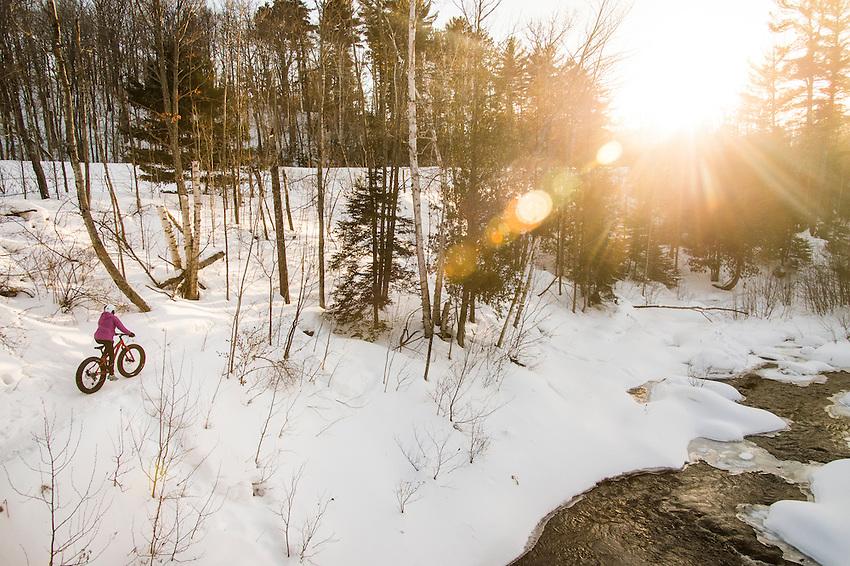 Winter cyclists on fat bikes ride snow trails along the Dead River in Marquette, Michigan.