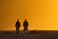 two friends walking along Okarito Beach, South Island, New Zealand