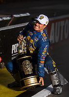 Nov 13, 2016; Pomona, CA, USA; NHRA funny car driver Ron Capps poses for a portrait as he celebrates with the world championship trophy the Auto Club Finals at Auto Club Raceway at Pomona. Mandatory Credit: Mark J. Rebilas-USA TODAY Sports