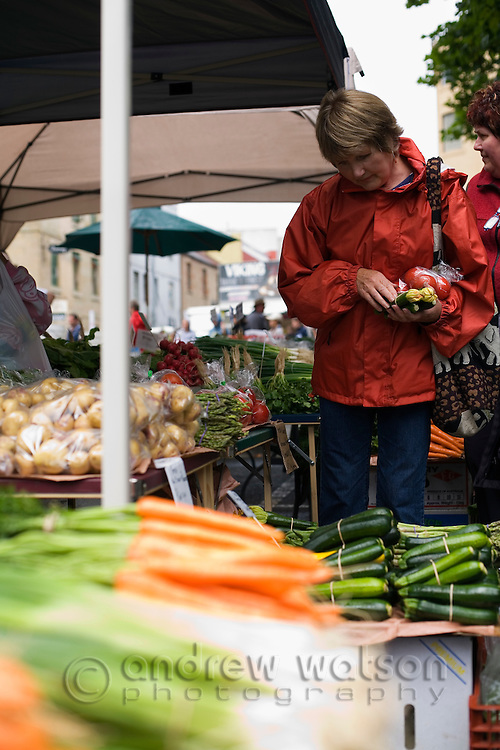 A woman shops for fresh produce at the Salamanca Market.  The weekly market, held in Salamanca Place, draws locals and tourists with its food and craft stalls. Hobart, Tasmania, AUSTRALIA