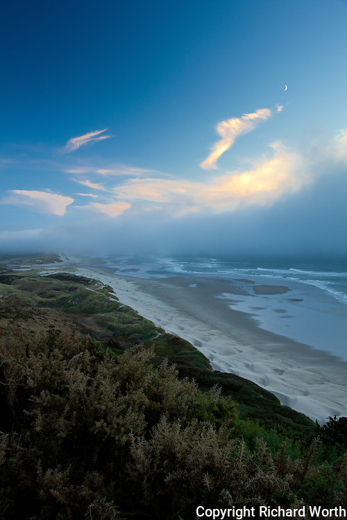 Clouds, tinged with sunet light, and a crescent moon  over the central Oregon coast.