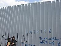 """TUNISIA dopo la rivoluzione: scritta """"laicità"""" su muro di Tunisi. Una coppia passeggia vicino al muro."""