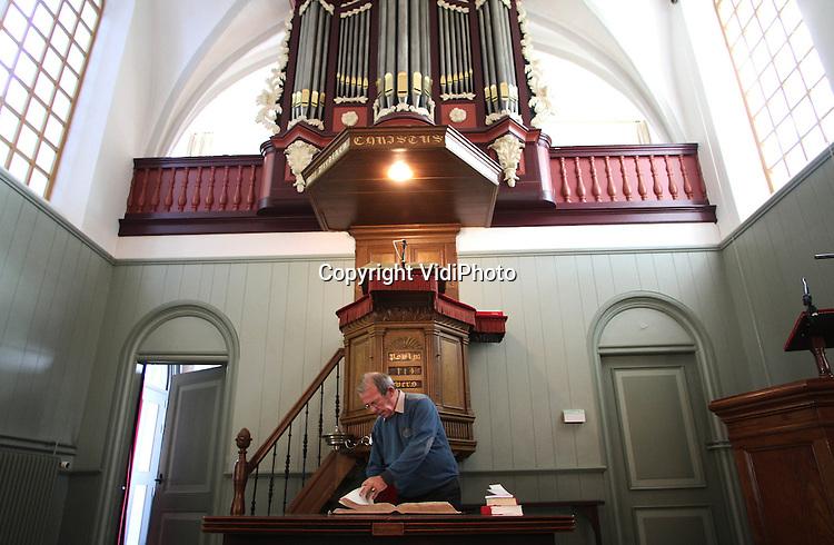 Foto: VidiPhoto..SLIJK-EWIJK - Een van de mooiste en karakteristieke kerken van Nederland gaat dicht: de witte kerk (14e eeuw) aan de Waaldijk in het Gelderse Slijk-Ewijk. De protestantse gemeente (PKN) fuseert met die van buurgemeente Herveld en daarmee wordt het goed onderhouden rijksmonument van de kleine kerkgemeenschap overbodig. Tot groot verdriet van de leden, overigens. Zondags bezoeken nog maar zo'n 20-25 mensen de dienst. Het liefst verkoopt de gemeente het godshuis voor 1 euro aan een kerkgemeenschap. Alle anderen dienen de taxatiewaarde te betalen. Die zal zo rond de 1,5 ton liggen. Zondag 30 december wordt de laatste dienst gehouden, in aanwezigheid van oud-predikanten. Door kerkverlating gaan er in de PKN gemiddeld iedere week twee kerken dicht. Foto: Ouderling-kerkrentmeester Gert Verhaaf zorgt er voor dat het interieur er tip-top uitziet voor potentiële kopers..