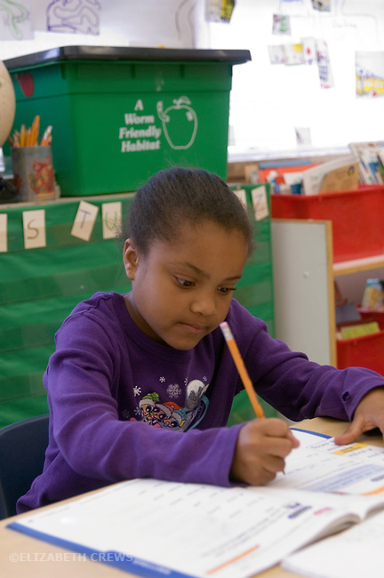 Oakland CA 2nd grade student absorbed in doing written work in class