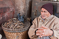 Kathmandu, Nepal.  Vendor of Dried Fish Awaits Customers, Durbar Square Market.  He wears a tikka on his forehead, a red mark serving as a blessing and a symbol of Hinduism.