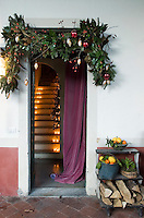 Spruce, baubles and winter berries decorate the doorway leading in from the courtyard
