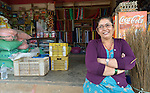"""Gita Giri sits in front of her shop in Adamtar, a village in the Dhading District of Nepal. Dan Church Aid, a member of the ACT Alliance, has provided food, shelter, livelihood, winterization assistance and a variety of other support to indigenous villagers here in the wake of a devastating 2015 earthquake. Giri was chosen by her neighbors to sell warm clothes, blankets and shelter materials which they could purchase with cash vouchers provided by the ACT Alliance. Giri made no profit on the sales. """"With people from around the world assisting our community, how could I make a profit on those supplies?"""" she asked."""