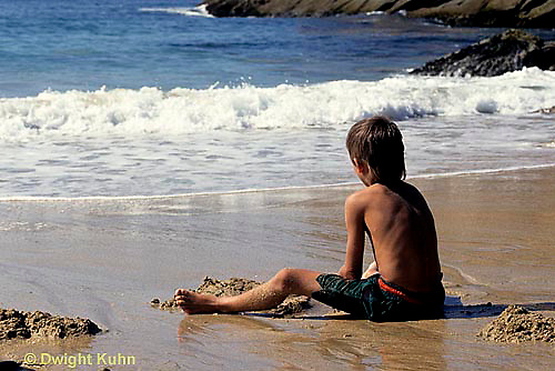 ON03-033z  Ocean - boy sitting on sandy beach watching waves breaking