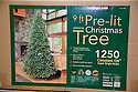 Packages of artificial Christmas tree with lights in store. California, USA