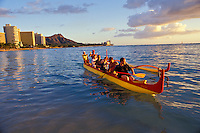 Tourists paddling an outrigger canoe off Waikiki with Diamond Head in the background