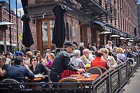 Busy al fresco dining at sidewalk cafes in the Meatpacking District in New York on Sunday, May 26, 2013. (©Richard B. Levine)