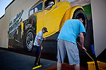 """James Devlin, left, and John Rainey clean a sidewalk in preparation for an American Graffiti Parade in Modesto, California, June 7, 2013. Modesto is celebrating the 40th anniversary of the film """"American Graffiti"""", with a parade headed up by native son, filmmaker George Lucas."""