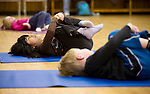 NAUGATUCK, CT--03 January 08--010308TJ02 - Laura Burns, 7 , center, hugs her knees to her chest during a yoga class with Mary Grant, 3, left, and Finbar Galvin, 5, all from Naugatuck, at the Naugatuck YMCA on Thursday, January 3, 2008. T.J. Kirkpatrick/Republican-American