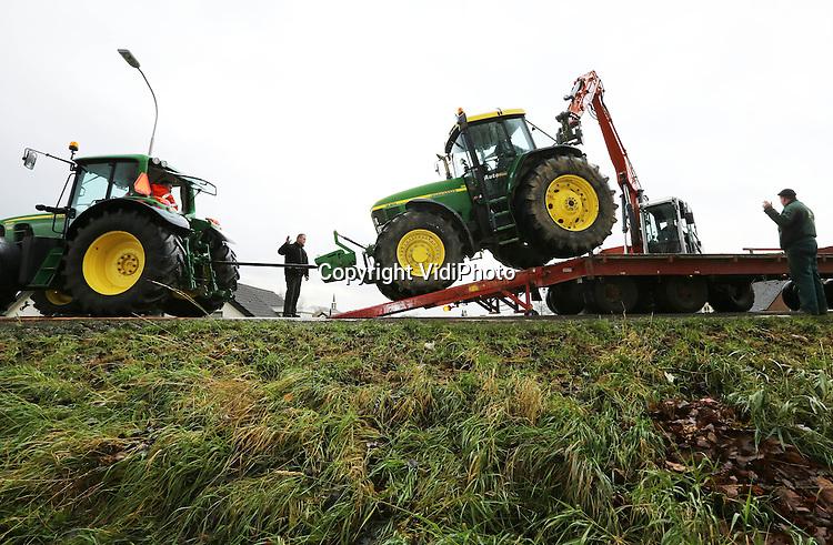 Foto: VidiPhoto..OPHEUSDEN - Spectaculair transport op de Rijndijk in Opheusden dinsdag. Noodgedwongen, dat wel, toen een tractor van loon- en grondverzetbedrijf Van Ossenbruggen BV uit Ingen door een breuk in het hydraulisch systeem midden op de dijk tot stilstand kwam. Om het gevaarte met aanhanger te kunnen verwijderen waren drie andere tractoren, een oplegger en een graafmachine nodig. Een groot deel van de ochtend was de Rijndijk bij Opheusden daardoor afgezet voor al het andere verkeer..