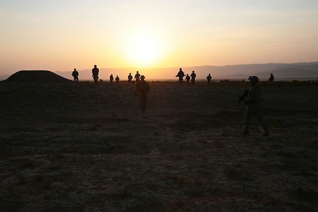 Soldiers with Company C, 4th Battalion, 23rd Infantry Regiment head out on an early morning patrol in the Shah Joy district of southern Afghanistan's Zabul province. The flat-topped hill on the horizon is all that remains of an ancient fort, an enduring symbol of Afghanistan's tumultuous history of foreign invasion and war. Oct. 27, 2010. DREW BROWN/STARS AND STRIPES