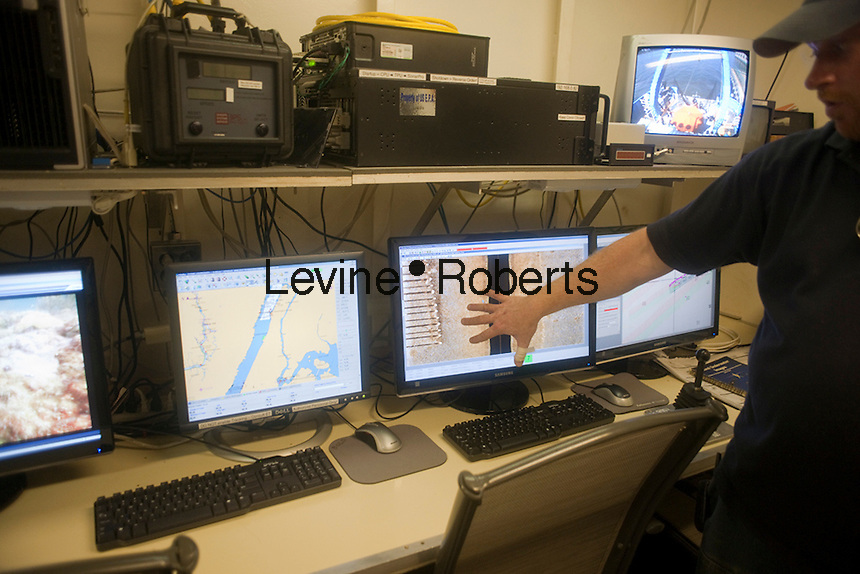 A crew member explains the sidescan sonar results on a computer screen aboard the Environmental Protection Agency OSV Bold in New York at Riverbank State Park on Saturday, July 31, 2010. The ship is the EPA' s only coastal and ocean monitoring vessel. Equipped with state-of-the-art technology the crew samples, monitors, maps and analyzes the impact of human activities, such as discharge, shoreline development and pollution, on oceans and coastal waters. (© Richard B. Levine)