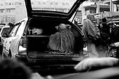 Kabul, Afghanistan<br /> November 2001<br /> <br /> A woman is loaded into the back of a car like baggage in central Kabul.