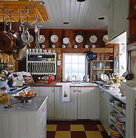 The clapboard family kitchen is festooned with vintage utensils and pottery found in local jumble sales