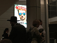 24. &quot;Polarities at Ben Gurion Airport&quot;: a Hasid ultra-orthodox Jew paired with secularized travelers who walk by an advert for polarized sunglasses, near Tel Aviv.<br /> <br /> As I prepare to return home after honoring my parents by planting a tree, I see this apocryphal scene at the airport. A Hasid is walking one way wearing traditional religious garb, while travelers dressed in more modern, secular clothing walk in the opposite direction. In the background, a spotlit ad features a fashionable young man wearing polarized sunglasses. <br /> <br /> Surely, this image highlights Israel's polarities! Looking at it, I wonder what values will ultimately triumph in this complex land.  Will superficial, destructive desires outweigh kindness and understanding? Will we ever make peace and find common ground?<br /> <br /> And will I go back to Israel to see what transpires?  I haven't decided. But I hope Israel will be there, despite its thorns and brambles, should I choose to return.