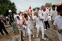 Elderly people lead a ceremony between graves with unclaimed bodies during a Thai Chinese ceremony at the Mang Teung Sua Jung Cemetery in Chonburi province southeast of Bangkok March 18, 2012. Every 10 years, hundreds of people wearing white, a customary colour for funerals and visiting temples, gather at this cemetery to exhume and cremate corpses as they believe they are helping the dead who have no friends or relatives. The ashes of the unclaimed bodies are spread on the sea to make room at the burial ground for more unclaimed bodies in the coming years. The tradition originated 90 years ago after diseases like Malaria killed many Thais of Chinese descent living in Chonburi.  REUTERS/Damir Sagolj (THAILAND)