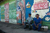 Mauritius. Men outside old building with graffiti.