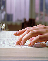 Woman's hand on the pages of a large reference book on her desk. research, reading, education. H. Bruce, M.R. H-1.