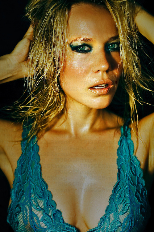 A young woman with wet blonde hair wearing a see through blue top