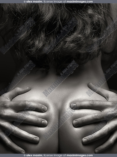 Artistic photo of a couple making love. Closeup of man's hands on woman's buttocks.